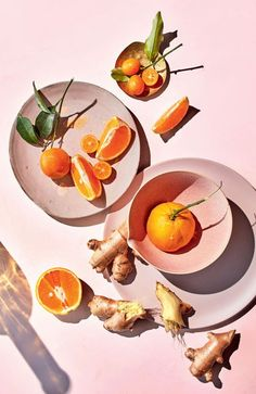 tangerines on pink backdrop in ceramic dishes. / sfgirlbybay