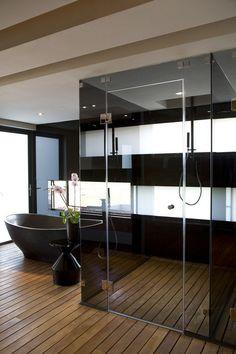 salle de bain noir et bois, revêtement de sol en bois massif, baignoire ovale et cabine de douche à l'italienne
