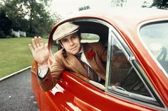 """Title: Elton John - Red Jaguar Caption: A shot of the musician waving taken in a fixed head Jaguar XK, during the """"A Single Man Sessions"""".   Artist: Terry O'Neill Date: 1978"""