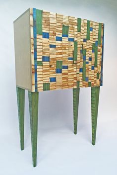 Skygazer Cabinet by Anne Bossert. The wood used in the Skygazer Cabinet is maple plywood. By stacking multiple pieces of plywood together and then cutting those stacks at different angles, various stripe widths are achieved. The small blue rectangles on the doors are the artist's hand-dyed, handwoven cotton fabric. The vertically striped plywood endgrain pieces on the doors, as well as the legs are dyed green. With the exception of two long, blue-dyed pieces of wood on the sides of the do...