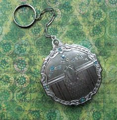 c1920s dance or tango compact. Round shape with carving along perimeter.  Rounded With Carved Out Sections. Repousse border, moire pattern and stripes on the bottom, garland of enameled forget-me-nots on top.