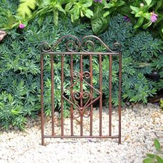 """Garden Gate by Structures. $4.59. material: Metal. size: 2.25"""" Wide x 4"""" High. What is the secret to fine gardening design? Sharing her knowledge of gardening, the Buttercup Fairy answered, """"Creating a focal point."""" The Garden Gate with its classical scroll metalwork creates the perfect focal point in any miniature garden."""