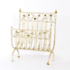 """In rustic antique white finish, this lovely metal magazine holder features a pretty rose design across the front and back. The ultimate shabby chic storage solution for your favorite magazines.   • 15.25""""L x 8.25""""W x 19.75""""H • Antique White • Metal"""