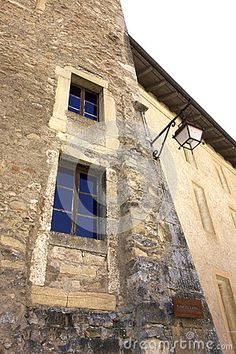 A closeup image of one of the old towers in the courtyard of Romainmôtier, Switzerland. Featured are old blue glass windows in a stone wall with a vintage street lamp. This is a Swiss heritage site of national significance. Street Lamp, Travel Europe, Heritage Site, Towers, Switzerland, Close Up, Cathedral, Old Things, Windows