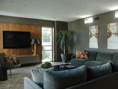 This modern gray living room features large canvas artwork, a plush sectional, a wooden accent wall and a mounted flat-screen TV.