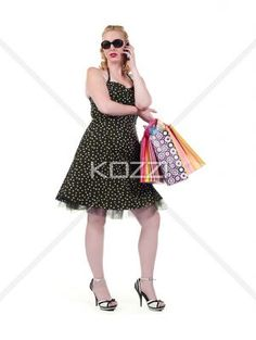 young blonde female with shopping bags talking over cellphone. - Portrait of a young blonde female with shopping bags talking over cellphone against white background, , MUA and Model: Amanda Wynne