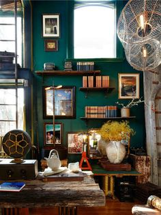 the profusion of color adds drama to this very masculine room . while it is a dramatic color, it does not dominate, but acts as a foil presenting the books and art to the viewer.  The frames and shelves seem to disappear against the wall so as not to distract the eye from the objects in or on them