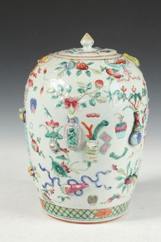 CHINESE FAMILLE ROSE PORCELAIN JAR AND COVER, 19th Century. Of ovoid form painted to depict flower-filled vases, precious objects and bat decoration in high relief, turquoise base - 13 in. high.