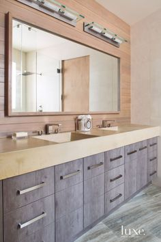 Concrete countertops from Concrete Design top Irpinia's American elm cabinets from Exquisite Kitchen Design in the guest bathroom. Door and drawer pulls are from Dornbracht, and a pine wall backs the room's custom mirrors.