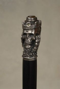 "Silver skull Memento Mori cane with jewels. The silver handle is 3"" high and 1 1/2"" at its widest point. It depicts a skull with a royal crown that has a 3/4"" faceted citrine in a bezel on top and seven small faceted emeralds around its sides. Bone hands are at the skulls cheeks in a pondering pose. The shaft is heavy ebony that is carved octagonally for its entire length and ends with a 1 1/2"" brass and iron ferrule. ca 1880. Perhaps Continental imported to America"