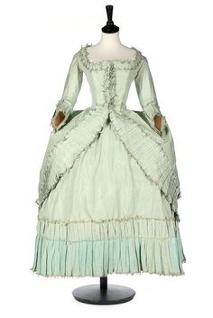 A peppermint-green silk 'Circassienne' robe, French, circa 1780, the over-dress with closed-front bodice, fastening with hooks and eyes, with with box pleated and fly-braid edged robings, fitted back and polonaised skirts with fixed green silk cords, worn over an above-ankle petticoat with deep pleated band to the hem