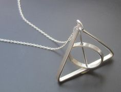A tribute to a classic tale, but also a fun unique pendant that MOVES! This pendant features a wand, a triangle and a circle all formed together to create an iconic tribute. Built as a kinetic sculpture, the sterling silver pendant has a spinning ring in the center that is pinned inside to