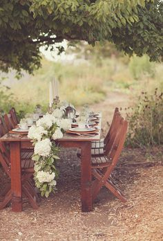 A white hydrangea table runner with greens, succulents, Annabelle roses, and baby's breath
