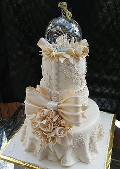 The cake tiers were 12 inch, 7 inch, and 6 inch. The edible gumpaste lace was created using a variety of purchased molds. Joe Martinez luster dusted the roses, bow, and leaves. The edible roses had non-edible stamen centers. The globe topper was a gift from the children to their parents.