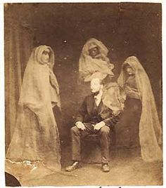 """Photographer: Frederick A. Hudson (England)  Mr. Raby with the Spirits """"Countess,"""" """"James Lombard,"""" """"Tommy,"""" and the Spirit of Mr. Wootton's Mother.    Albumen Print, 3.5 x 4 inches    circa 1875"""