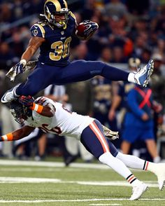Todd Gurley #30 of the St. Louis Rams leaps over Antrel Rolle #26 of the Chicago Bears as he carries the ball in the first quarter at the Edward Jones Dome on November 15, 2015 in St. Louis, Missouri