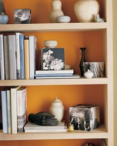 I think I like the idea of a very muted, pastel orange wall paint with a more vibrant orange on the inside of our bookshelf (which needs repainting anyway). Less trendy than an accent wall.