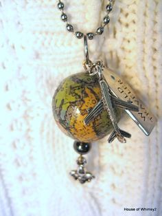 World traveler necklace.  She decoupaged vintage bits of map onto a round bead, and then added the other findings. (House of Whimsey 2)
