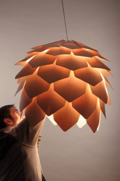 Crimean pinecone by designer Pavel Eekra is an incredible construction of  semi-transparent veneers of natural maple. These wooden scales are cut so very thin that they stop just short of transparent, yet they're perfectly sufficient to let the lovely illuminations shine through- the new 'aspen artichoke'?