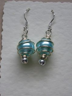 Sterling Silver ear wires with a silver plated cage containing a turquoise glass pearl and completed with small silver beads