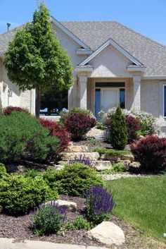 Shrubbery and purple salvia fill the front yard landscape of this home with rich color. The green and burgundy shrubs provide color all year long while the salvia is a seasonal interest throughout the yard. Sloped Front Yard, Landscaping A Slope, Inexpensive Landscaping, Landscape Lighting Design, Curb Appeal, Garden Design, Backyard, Brick, Gardening
