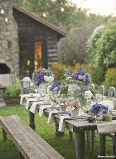 A lovely rustic outdoor intimate wedding tablescape with chairs on one side and a bench on the other side