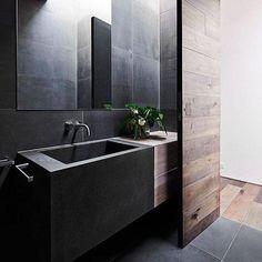 Minimaler Badraum in Schwarzem, das mit zurückgeholtem Holz weich gemacht wird