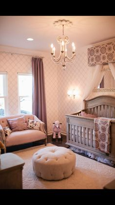 This nursery features a subtly ornate style, courtesy of patterned wall covering, carved wood and button tufted love seat and circular ottoman, and immense natural carved wood crib. Wall sconce and chandelier light the space. how to afford a baby Baby Bedroom, Nursery Room, Girls Bedroom, Baby Rooms, Nursery Decor, Room Baby, Kids Rooms, Nursery Furniture, Children Furniture