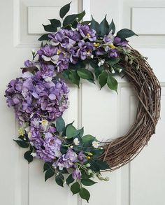This purple floral wreath is perfect for spring. The purple flowers range between lighter and darker shades of purple. Small white flowers are interspersed throughout. Flowers are attached to a grapevine wreath with wires. The wreath measures approximately 24 inches from top to bottom and 22 inches across. Both measurements include foliage.