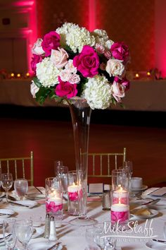 Tall glass centerpiece with hot pink flowers and floating candle dishes #wedding…