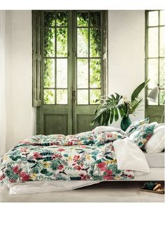 Wake up in this botanical bedroom with colorful bedding and green plants.