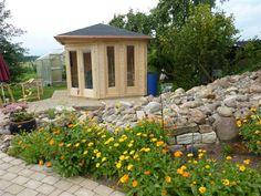 Ganz natürlich: Dieses 5-Eck-Gartenhaus in Naturholz passt perfekt zu der Steinmauer und dem frischen Beet im Garten.
