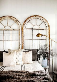 Great idea. Use vintage window frames as a one of a kind headboard.
