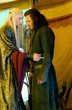 It looks like Thranduil is either helping him dress or complaining about said outfit. That belt with this coat? Please.