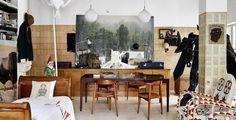 Schrift-Bild: In seinem Atelier hat Alba einen Teil der Wände mit alten Buchseiten verkleidet. Unverkennbare Alterungsspuren zeigen auch die lederbezogenen Wegner-Stühle. Die beiden Massai-Throne rechts sind Mitbringsel aus New York.