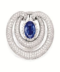 SAPPHIRE AND DIAMOND BROOCH. Centring on an oval sapphire weighing 11.64 carats, to a stylised surround pavé-set with brilliant-cut diamonds together weighing approximately 10.65 carats, with pendant fitting; mounted in 14 karat white gold