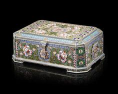A large silver-gilt and enamel trunk-form box, 11th Artel, Moscow, 1908-1917. Decorated in polychrome filigree enamel featuring Usolsk-style pink blooms with green foliage, borders outlined with geometric motifs in translucent and matte blue and green enamel, highlighted with clusters on granulation and elaborate wirework,  the verso of the lid is counter-enamelled in bright red over sunburst engine turned ground.