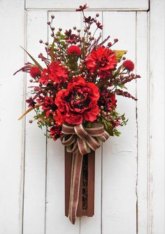 Welcome the season with this unique, one of a kind alternative to a door wreath or door swag. I designed this starting with a wood crate base. I added artificial greenery, red/burgundy peony and hydrangea. Rust glitter berry picks accent the burgundy colors. A rust, glitter gold tan