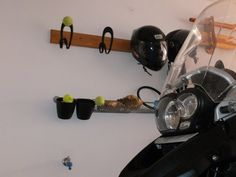 IKEA Hackers: Easy DIY helmet hanger. Ikea curtain hooks nailed to wood! Can be used for motorcycle or bike helmets. Also check out the tennis ball holders.