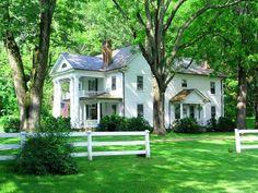Farmhouse, white fence, and big shade trees