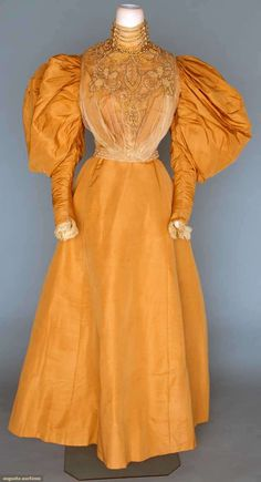 "Reception gown, 1895-96; Two piece, gold silk faille, bodice with high neck, white chiffon overlay, front embellished with crystal beads and pearls, cream silk lining, petersham label ""Sprague Battle Creek"", skirt, built in bustle pad"
