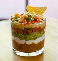 Seven layer dip shots -- great for a party so people don't have to be crowded around a big bowl of dip. Layers: 1. Refried Beans  2. Sour Cream  3. Guacamole  4. Pico De Gallo  5. Queso Dip  6. Cheese  7. Green Onion