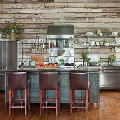 Rustic Lake House Kitchen | To complement the rustic wood wall, Designer Richard Tubb chose freestanding restaurant-grade stainless steel cabinetry and enlisted blacksmith Darren Hardman to craft a custom steel island. | SouthernLiving.com