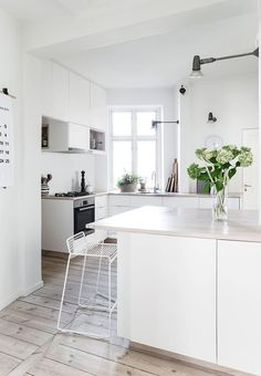 Soft and bright homemade kitchen with 23 angles and kitchen cabinets from Ikea cut to fit the angles. The table top is made of old floorboards, while the stools are from Hay.
