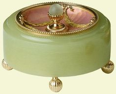 A Fabergé circular bell push of bowenite with concave salmon pink guilloché enamel bowl set with four garlands of green gold, the centre has a gadrooned gold finial with a matt mecca stone push, all set on four circular gadrooned gold feet. Mark of Henrik Wigström, 1908. Probably acquired by King Edward VII and Queen Alexandra.