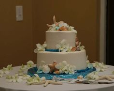 Shells, starfish and flowers surround the delicious wedding cake