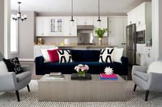 Contemporary living room features a dark blue velvet sofa lined with black and white pillows facing a long metal cocktail table flanked by gray accent chairs atop a gray maze rug.