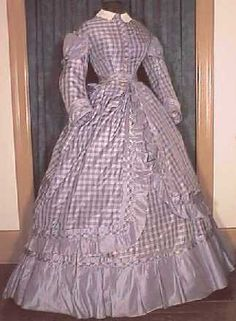 A lovely lavender plaid taffeta circa 1865 to 1867 lady's dress with matching overskirt. In the classic silhouette of the late to post War period.