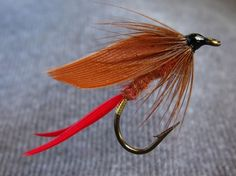 107)-Fiery-Brown- Tag, flat gold tinsel, Tail, crimson quill fibres, Body, fiery/rusty brown wool/dubbing, Wing, paired brown slips, Front hackle, soft brown (hen) hackle.