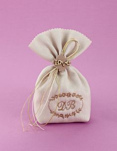 www.mpomponieres.gr Μπομπονιέρα γάμου πουγκί από υψηλής ποιότητας ύφασμα πικέ μπεζ με τελείωμα ζικ-ζακ, δεμένο με δύο κερωμένα κορδόνια και ένα σπαγγάκι σε μονό φιόγκο, διακοσμημένο με μπάλωμα όπου έχει κολλημένο ξύλινο love και κεντημένο στεφάνι με μονογράμματα. Τα χρώματα στις μπομπονιέρες κατόπιν συνεννόησης μαζί μας μπορούν να προσαρμοστούν στην προτίμησή σας. #mpomponieres #bombonieres #gamou #gamos #bonbonieres #μπομπονιερες #γαμου #γαμος